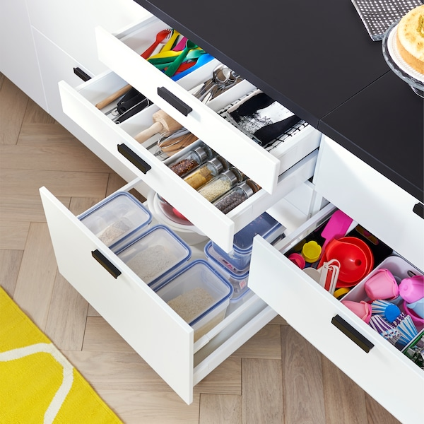 Kitchen with open drawers in white that display plastic food containers, kitchen utensils and colorful kitchen tools inside.