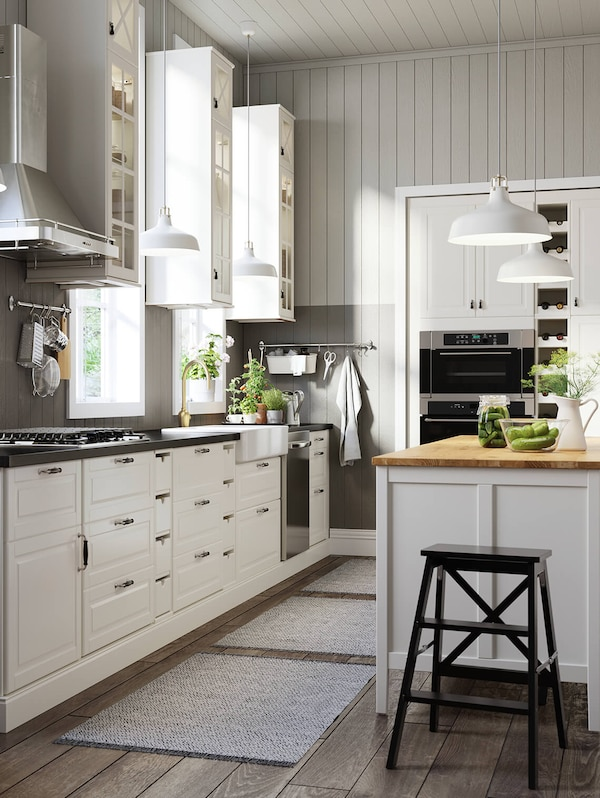Kitchen with white cabinets and an island with multiple white pendant lamps