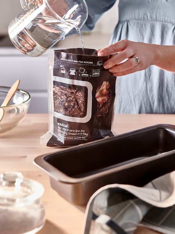 Kitchen worktop with a HEMMABAK loaf tin and other baking accessories. Hands pour water into a bag of KNÅDA baking mix.