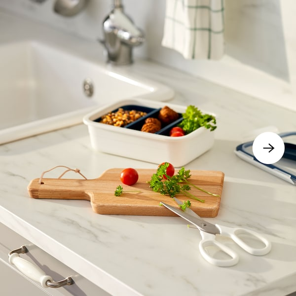 Kitchen worktop with a meal divided into compartments of a lunch box, a chopping board with tomatoes and freshly cut herbs.