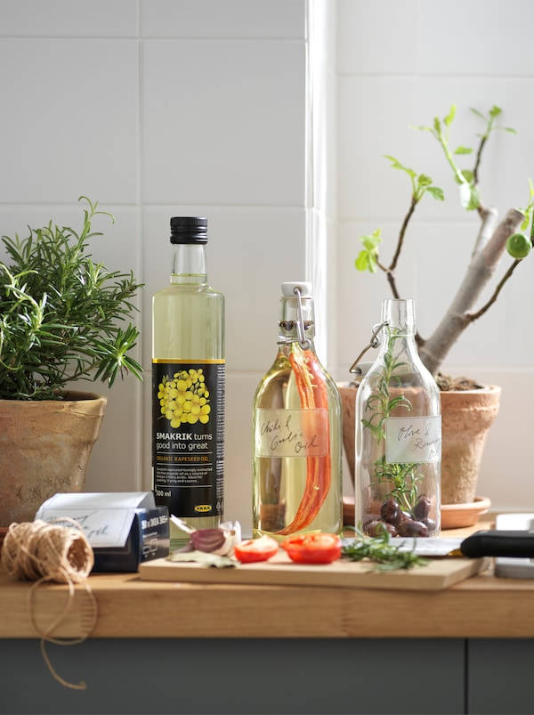 Kitchen worktop with plant pots and two KORKEN glass bottles, mid-session of infusing rapeseed oil with spices and herbs.
