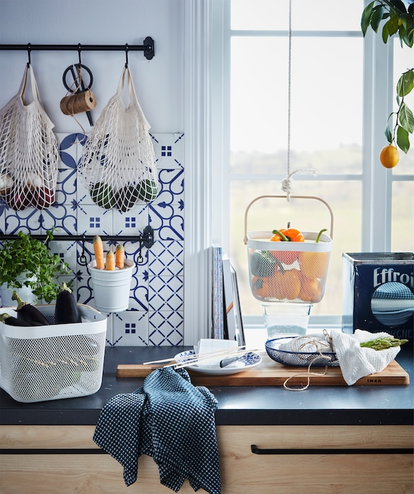 Kitchen worktop with various food produce kept in hanging and standing containers.