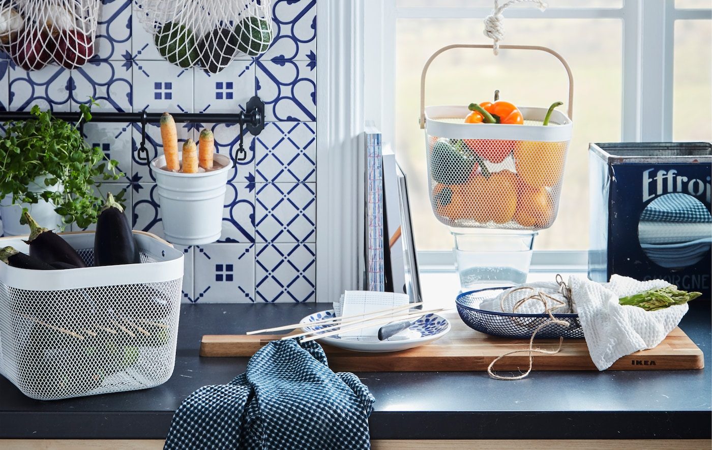 Kitchen worktop with various food produce kept in hanging and standing containers, like KUNGSFORS nets and RISATORP baskets.