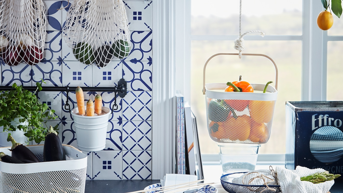 Kitchen worktop with various produce kept in hanging and standing baskets, like KUNGSFORS nets and RISATORP baskets.