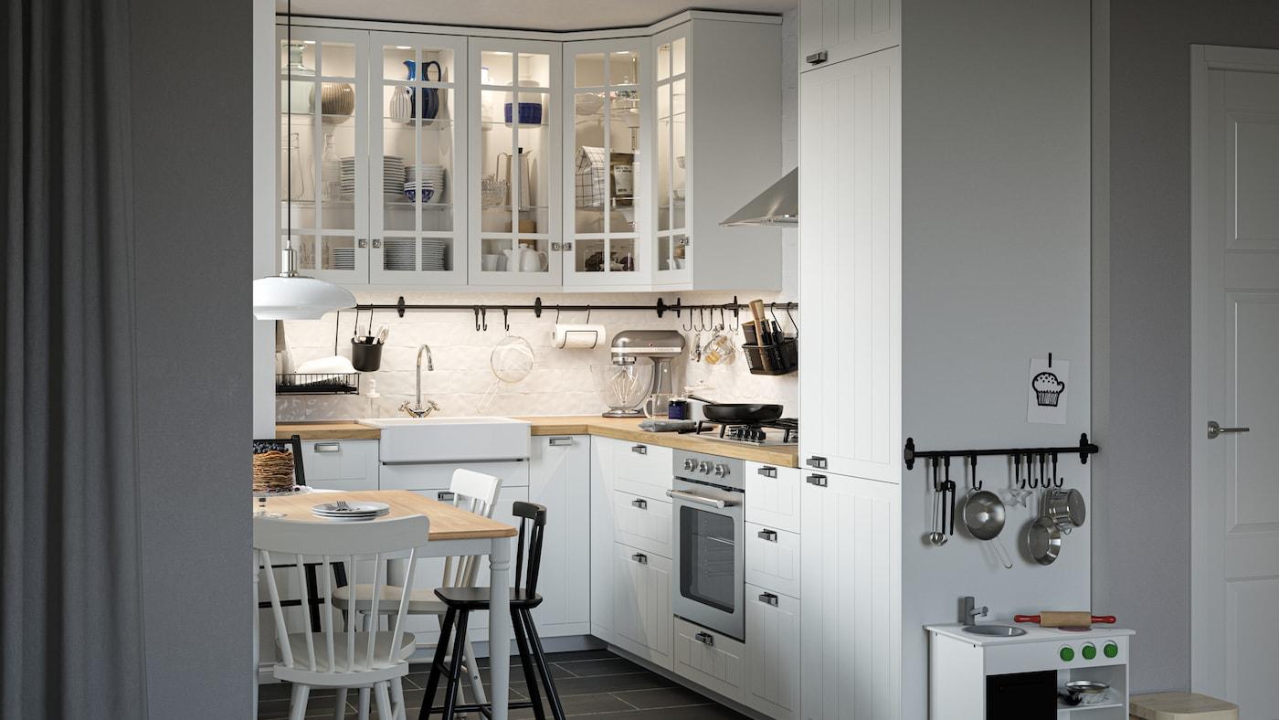 Kjøkken i tradisjonell stil med hvite fronter og skap med vitrinedører, spisebord, stoler og et lekekjøkken.