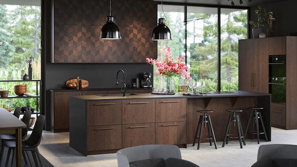 Kjøkken med åpen planløsning med vinduer fra tak til gulv, SINARP skuffer og HASSLARP dører, svarte taklamper og barkrakker.