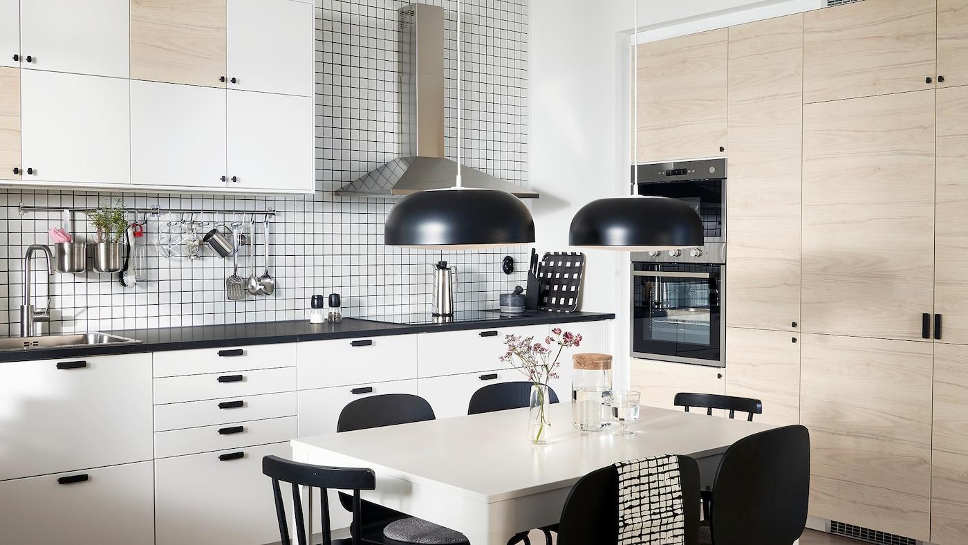 Kjøkken med dører i hvitt og lyst askemønster, to svarte taklamper, hvitt bord og svarte stoler.
