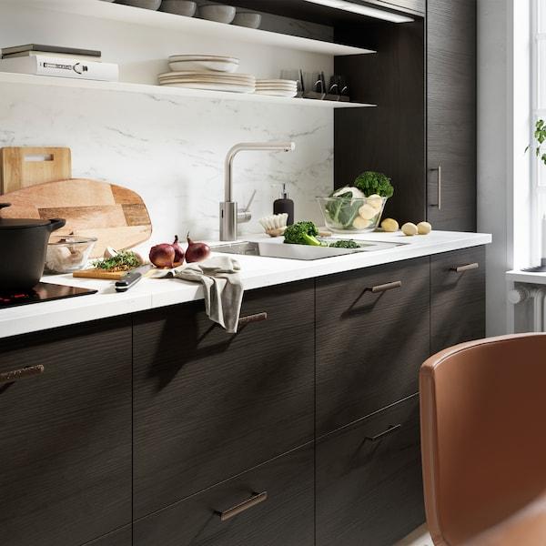 Kjøkken med veggplate og benkeplate i hvitt marmormønster, kjøkkenfronter med mørkebrunt askemønster og svarte håndtak.