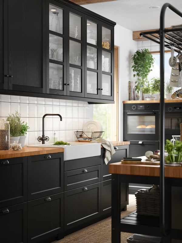 Kjøkken med vitrinedører med svartbeisede trerammer, skap med svartbeisede fronter og benkeplate av tre.