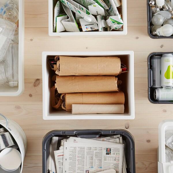KLÄMTARE plastične posude, okružene kutijama za odlaganje, punim reciklažnog materijala, na drvenoj površini.