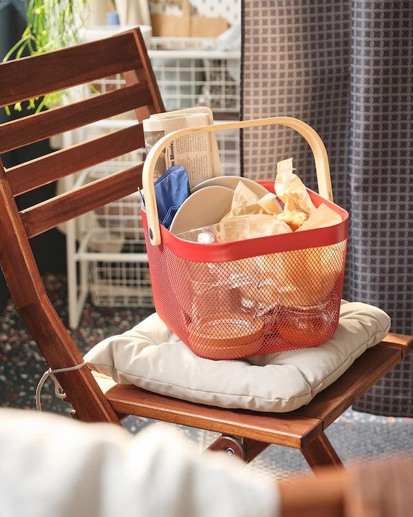 Klappstuhl auf einem Balkon. Auf dem Stuhl steht ein RISATORP Korb in Rot.
