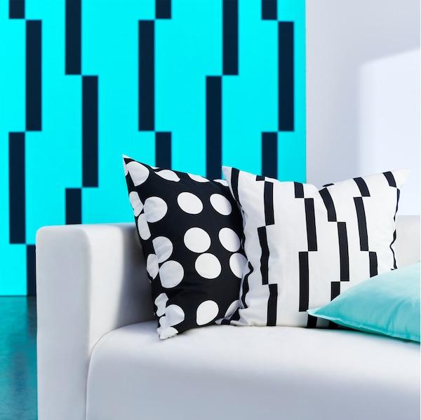 KLARASTINA Kissenbezug mit Punkten und KINNEN Kissenbezug mit geometrischem Muster, beide in Schwarz und Weiß.
