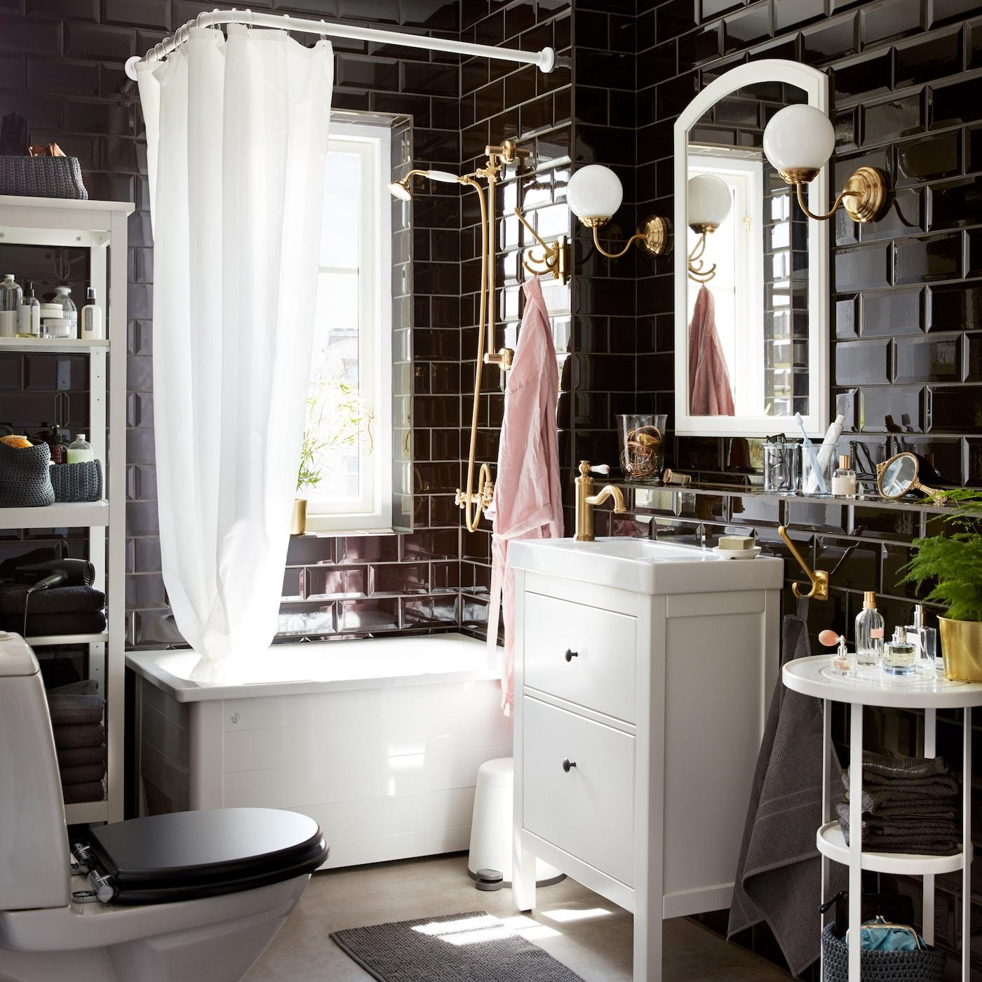 Klassinen kylpyhuone, jossa mustat laatat ja valkoiset kalusteet.