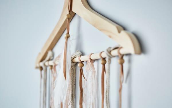 Kleiderbügel aus Holz an einer Wand mit vielen Schnüren daran befestigt.