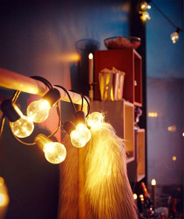 Kleiderstange mit einer SVARTRÅ Lichterkette neben einem Wandbereich mit mehreren Regalen