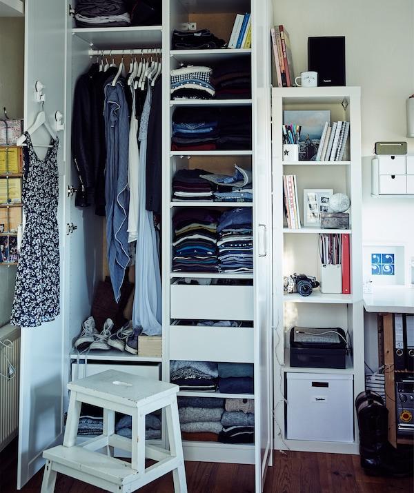 Kleidung auf Regalböden und auf der Stange in Stines PAX Kleiderschrank in Weiß mit FORSAND Fronten in Weiß