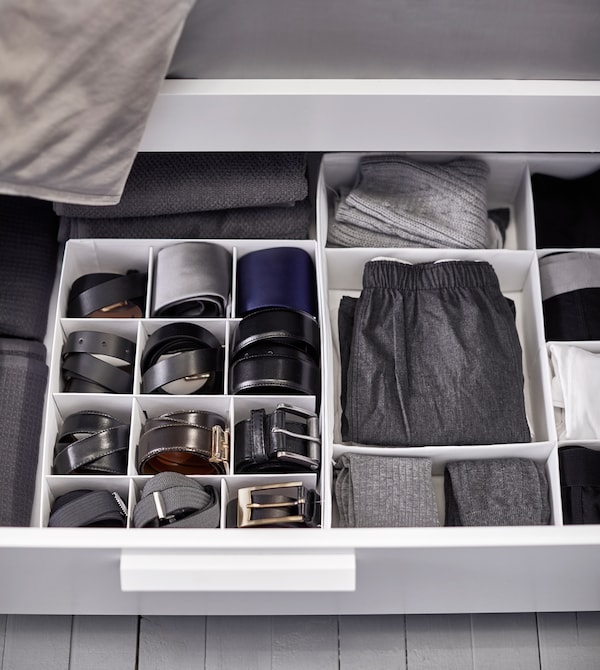 Kleidung und Gürtel ordentlich sortiert in TJENA Kasten mit Fächern in Weiß unter einem Bett