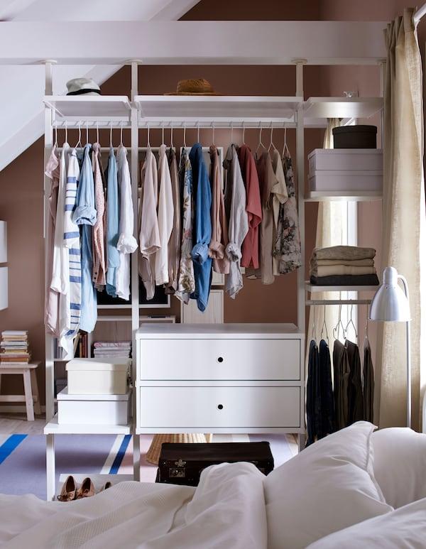 Kleidungsaufbewahrung als Raumteiler mit hängender und gefalteter Kleidung, u.a. mit ELVARLI Kleiderstange in Weiß.