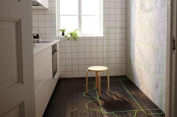 Kleine keuken met een onafgewerkte wand waarop met groene plakband de toekomstige plaatsing van de opbergmeubelen, tafels en stoelen wordt aangeduid