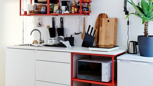 Kleine rood-witte keuken met een draagbare inductiekookplaat, houten snijplanken en een zwart afdruiprek.