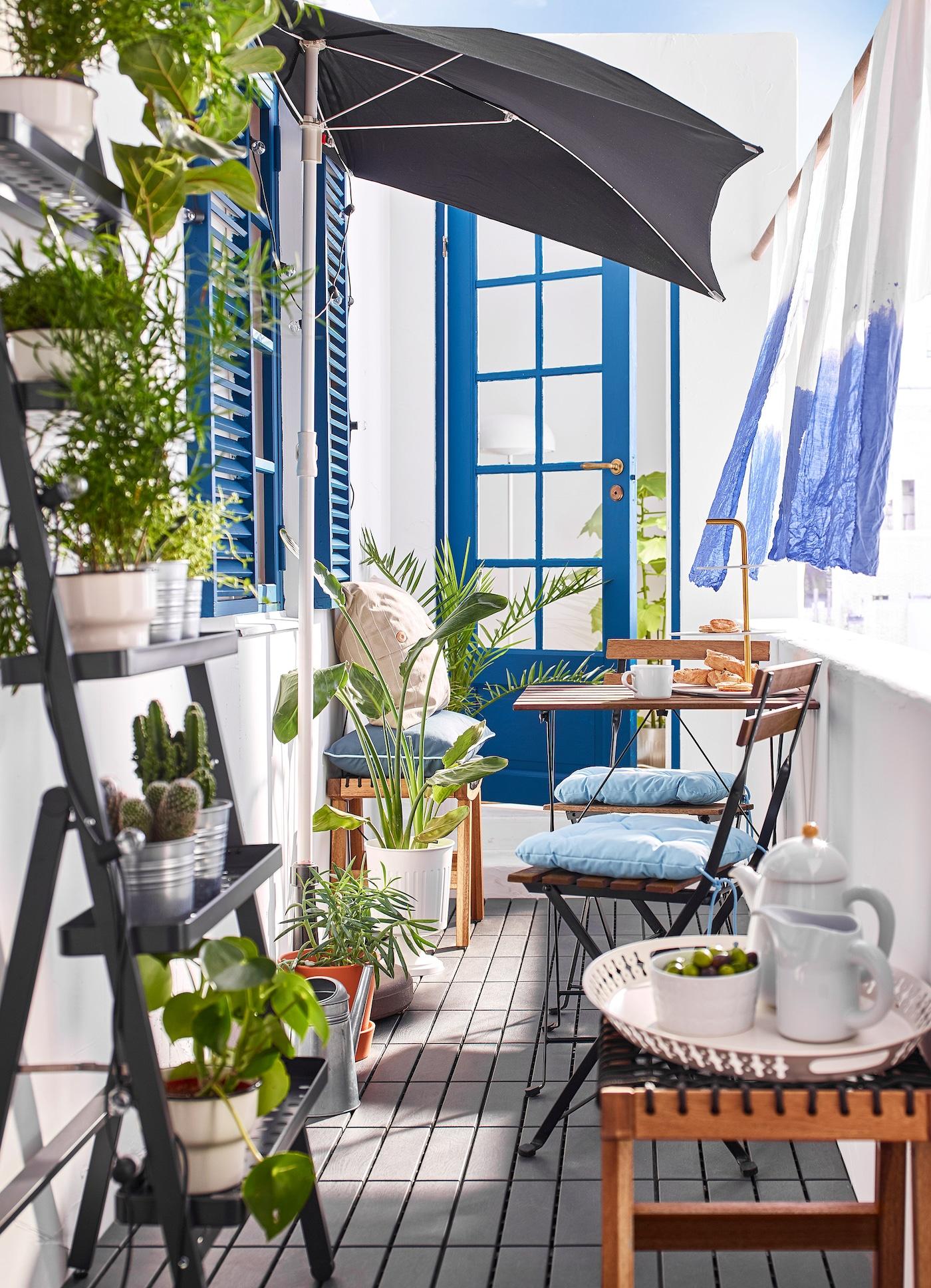 Kleiner Balkon mit Tisch, Stühlen, Pflanzen, Sonnenschirm & vielen kleinen Dekoartikeln.