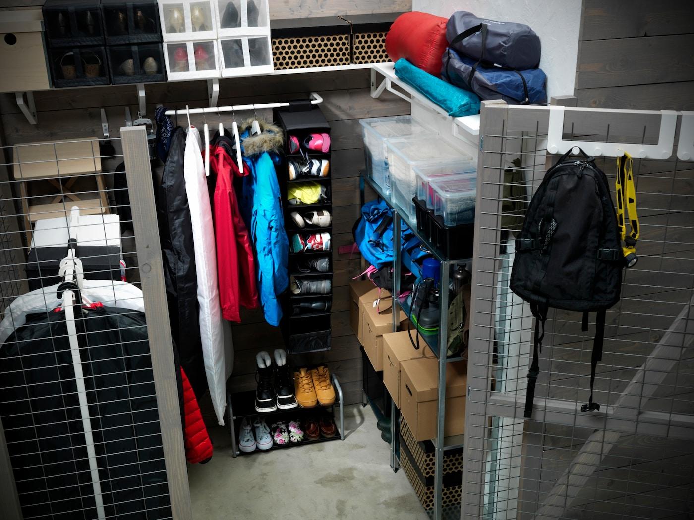 Kleiner, grauer Kellerraum mit Regalen, Kleiderstange, Schuhkartons, Schuhen & Rucksack.