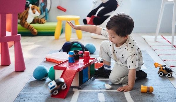 Kleiner Junge, der auf dem Boden spielt, umgeben von Spielzeug.