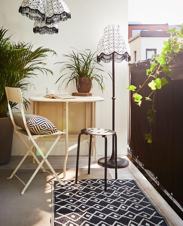 Kleiner Sitzbereich auf einem Balkon, abgeschirmt durch DYNING Sichtschutz für den Balkon in Schwarz.