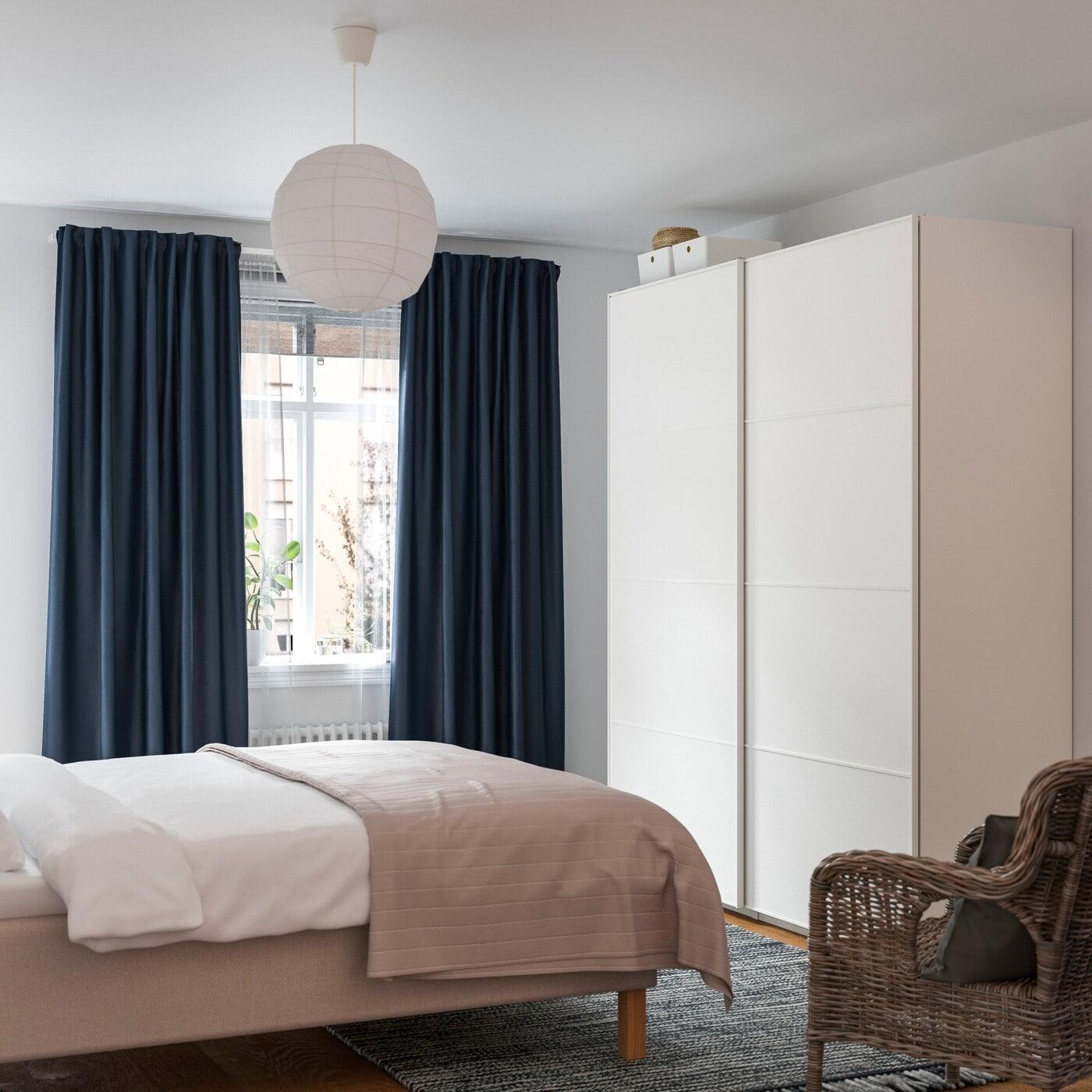 Kleines Fenster im Schlafzimmer mit einer Vorhanglösung in Dunkelblau