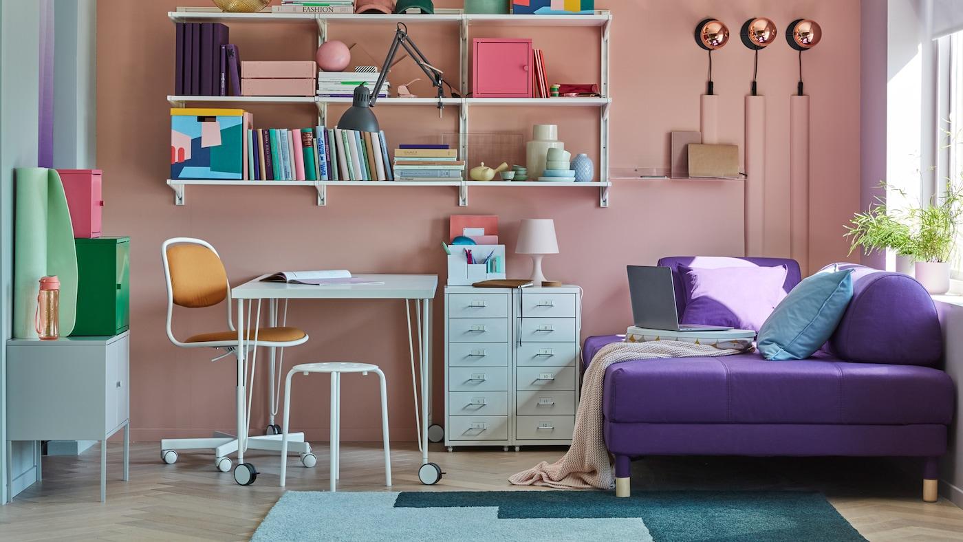 Kleines Zimmer, bestehend aus Wohn- und Arbeitsbereich, mit einer bunten Farbgestaltung.