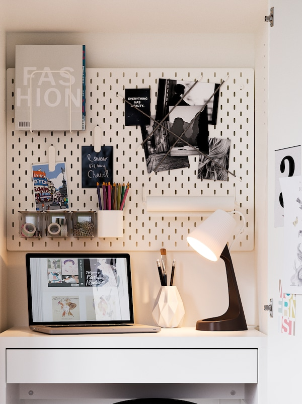 KLEPPSTAD wardrobe fashioned to be a very compact workspace, with a SKÅDIS pegboard holding accessories, and a SVALLET lamp.