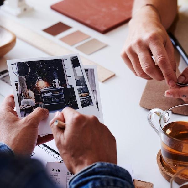 Klient pokazuje zdjęcia inspiracyjne pracownikowi IKEA.