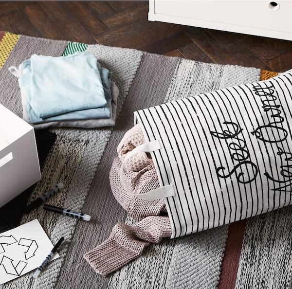 KLUNKA-pyykkikassi, joka on täytetty paidoilla, valkoisella laatikolla ja pinolla vaatteita, kaikki levitettynä harmaalle matolle.
