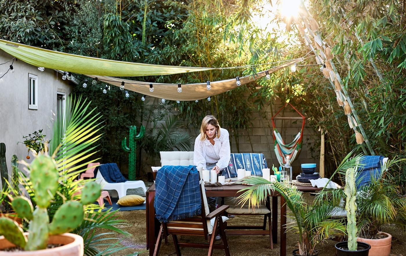 كلوي تقوم بترتيب الطاولة في الخارج في حديقتها، مع أثاث خشبي ونباتات وأشجار ومظلات مع سلاسل إضاءة.