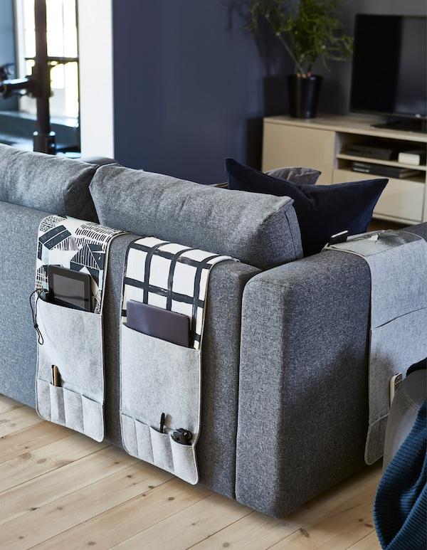 KNALLBÅGE grey felt sofa organisers hang on the back of a grey sofa in this living room.