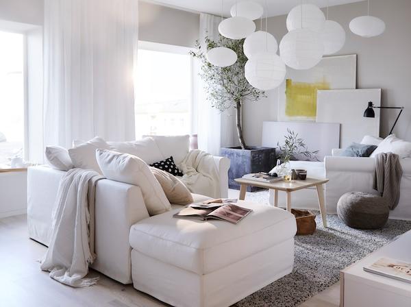 كنبة GRÖNLID بيضاء وأريكة استرخاء وطاولة قهوة خشبية فاتحة LISABO في غرفة جلوس بيضاء.