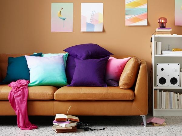كنبة جلد أصفر/بني مع وسائد وردي، وأرجواني وأخضر، وغطاء وردي وصور ألوان باستيل على الحائط.