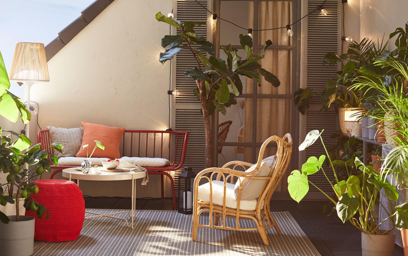 كنبة للأماكن الخارجية 3 مقاعد BRUSEN من ايكيا وكرسي بذراعين روطان في مساحة شرفة خارجية، مع نباتات ومصباح أرضي.