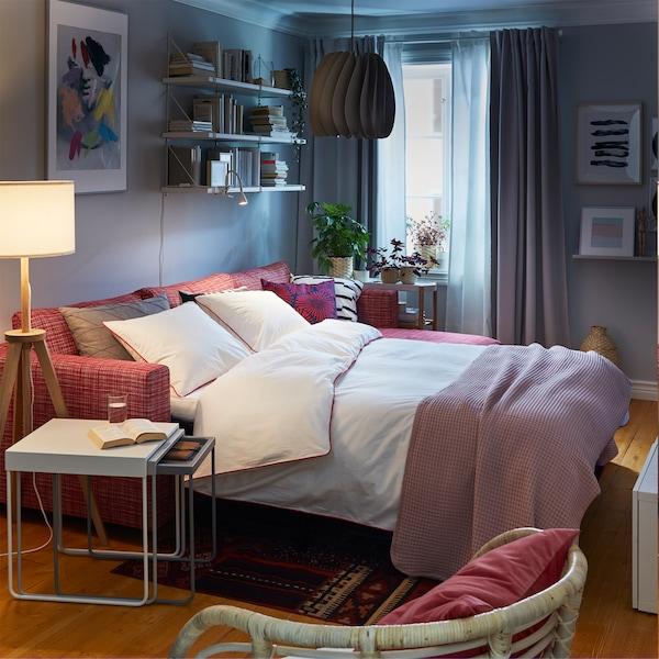 كنبة سرير أحمر مرتّبة في وضعية السرير مع منسوجات سرير بيضاء، ومجموعة طاولات بيضاء ومصباح أرضي خشبي أبيض.
