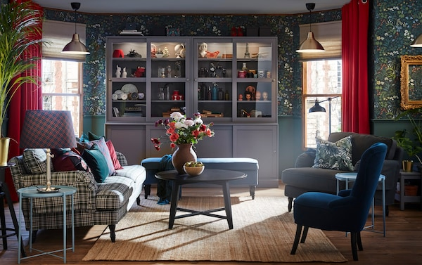 كنبة STOCKSUND ومقعد أزرق زاهي في غرفة جلوس بها ورق حائط زهور مزينة بمربعات وستائر مخملية أحمر زاهي.