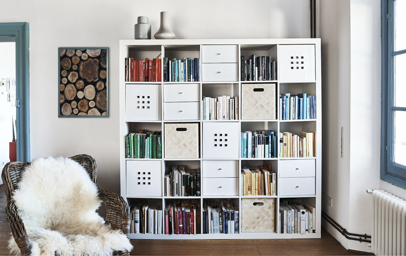 Книги и коробки в шкафу, словно составленном из кубиков.