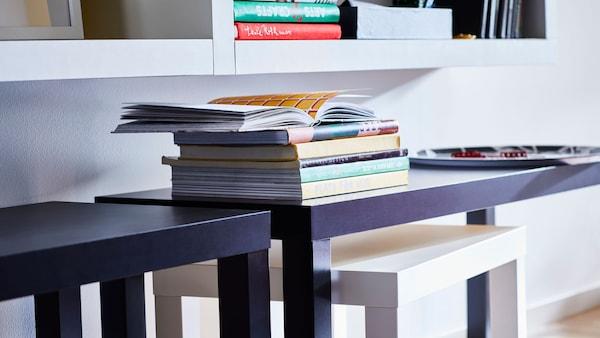 Knihy a časopisy rozložené po stolcích LACK.