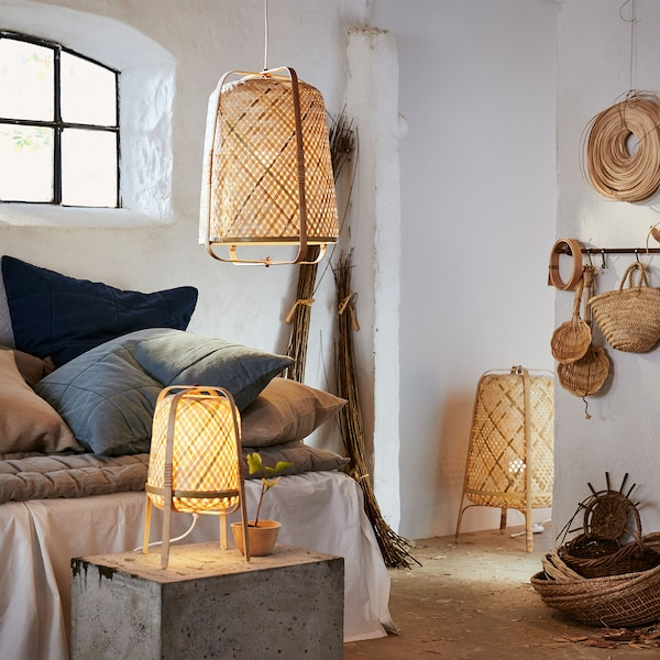 KNIXHULT bamboo floor, pendant and table lamps are shown in a white room. They are woven and have exterior bent accents.
