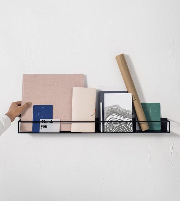 Knjige i pribor na crnoj polici za izlaganje.