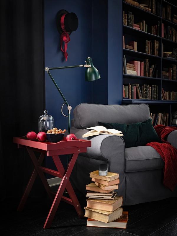 Knjige su naslagane na police pored udobne EKTORP fotelje, a crveni sto i zelena lampa nalaze se odmah pored fotelje.