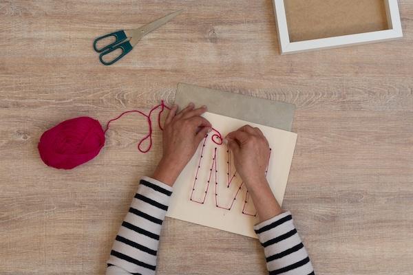 Knote den Faden an einem Nagel fest und wickle den Faden um die Nägel, die den Rand des Motivs bilden.
