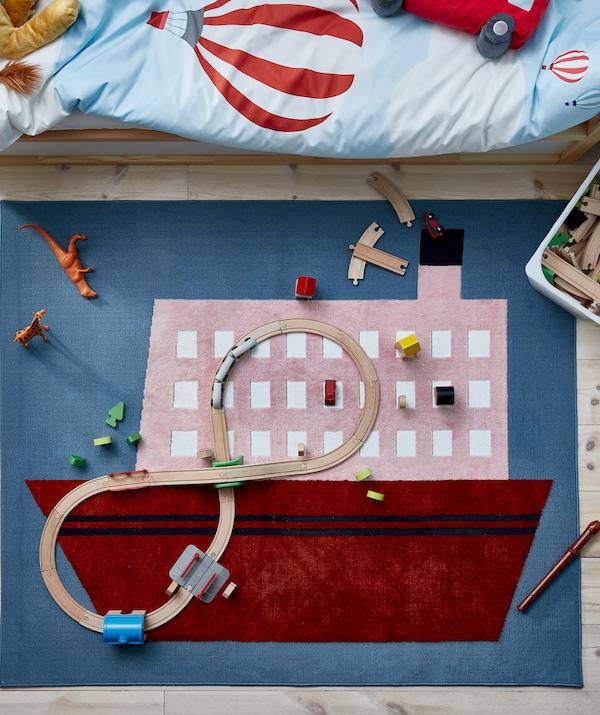 Koberec s motívom lode umiestnený pri detskej posteli s drevenými dielmi vláčika a ďalšími hračkami.