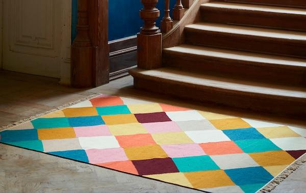 Koberec VINDERÖD s farebným károvaným vzorom položený pod schodami z tmavého dreva s prepracovanými detailmi.