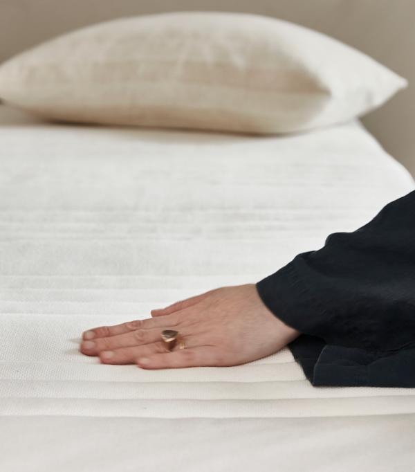Kobieca dłoń na materacu MATRAND