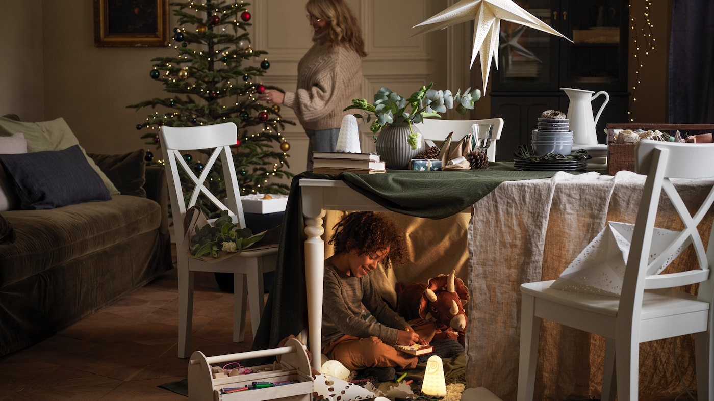Kobieta dekoruje drzewko bożonarodzeniowe, a pod widocznym na pierwszym planie, częściowo zakrytym tkaninami stołem chłopiec bawi się zabawkami.